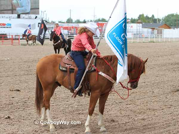 A Cheyenne Dandie dips her flag in respect to the flag of the United States  of America