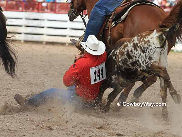 A steer wrestler gets down on his steer