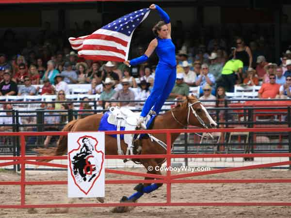 A trick rider carries an American Flag