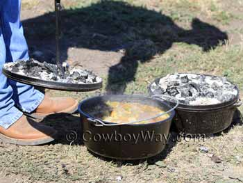 Camping Dutch ovens with coals on their lids