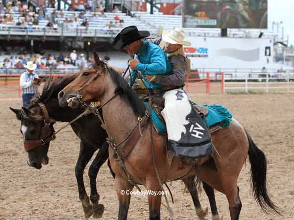 Saddle bronc rider Dusty Hausauer gets off on a pickup man