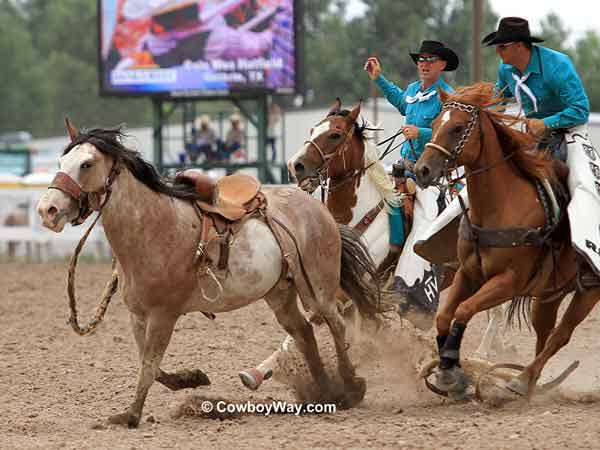 Pickup men move in on a saddle bronc