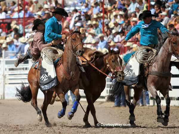 A saddle bronc rider gets off with help from the pickup men