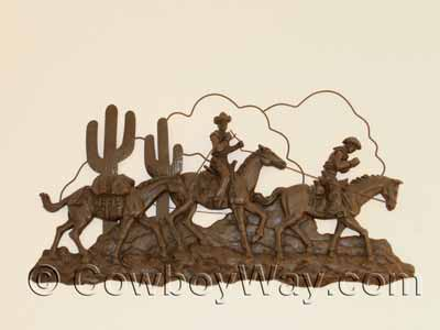 Cowboys and pack horses metal art on a wall