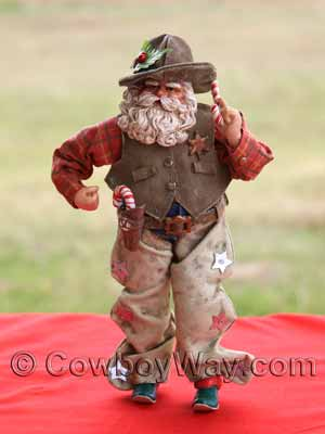 A cowboy Santa figurine with mistletoe and candy canes