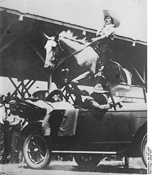 Unknown cowgirl jumping a horse over a car