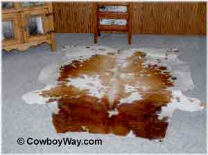 A cowhide rug on carpet