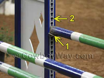 Close-up photo of jump standards showing keyhole tracks