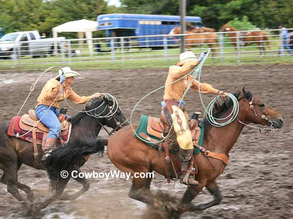 Two cowgirls gallop down a muddy arena