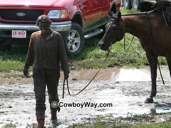A lone cowgirl covered in mud and her horse