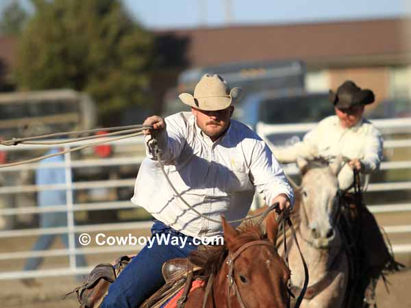 Two cowboys concentrate on roping a steer