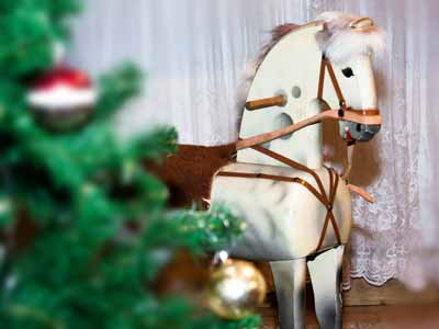 A large wooden rocking horse by a Christmas tree