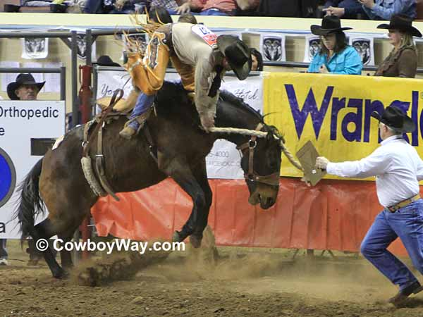A rider makes a sudden dismount in the saddle bronc riding