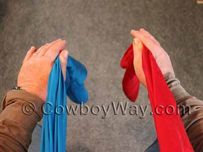 Begin tying the wild rag knot with the tails of the wild rag at your front