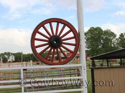 A wagon wheel as decor at a ranch gate