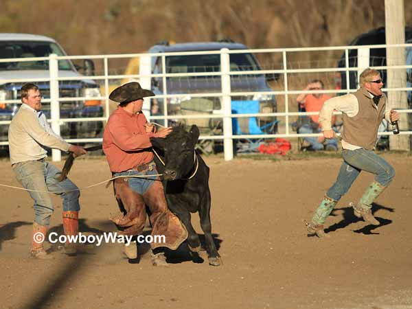 A cowboy runs with a bottle of milk to the judge