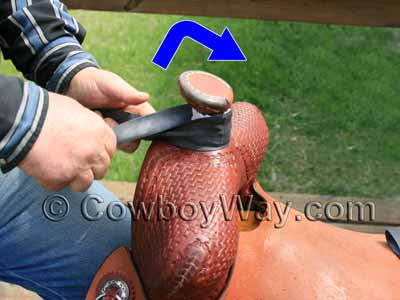 Twist the rubber then loop it up and over the saddle horn