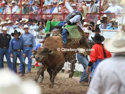 A bull rider in green chaps and a bull riding vest