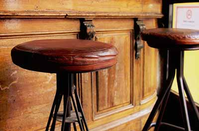 Cowhide bar stools with brown leather seats and swivels