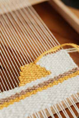 Hand weaving a tapestry